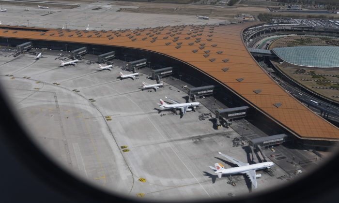This aerial view taken through the window of a plane, shows various Airbus A330 and Boeing 737 planes of Air China parked at Beijing's capital airport on April 11, 2018. (Greg Baker/AFP/Getty Images)