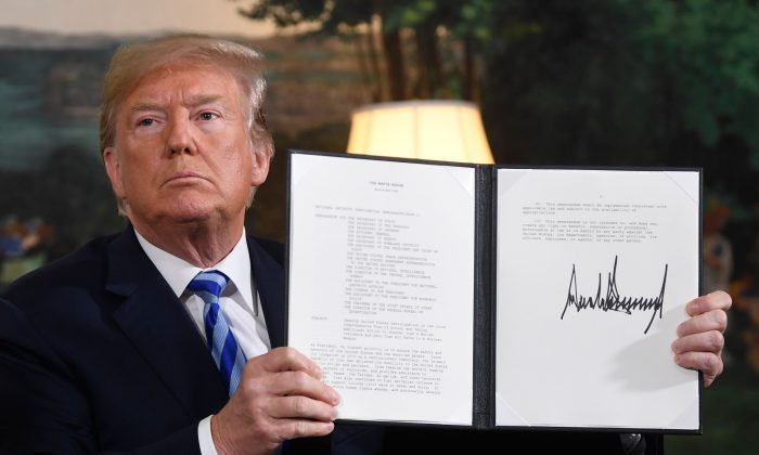 President Donald Trump signs a document reinstating sanctions against Iran after announcing the US withdrawal from the Iran Nuclear deal, in the Diplomatic Reception Room at the White House in Washington, D.C., on May 8, 2018. (Saul Loeb/AFP/Getty Images)