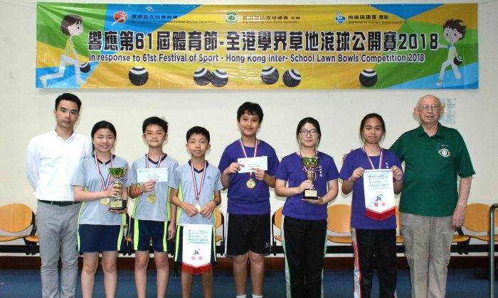 (L) Mr Law Hang Kong of the Hong Kong Leisure and Cultural Services Department, and (R) Mike Worth, Treasurer of HKLBA, presented the Inter-schools Lawn Bowls Competition awards to teams from Yan Oi Tong Tin Ka Ping Secondary School (in purple shirts) and Lutheran Tsang Shing Siu Leun School (in grey shirts). on Tuesday May 1, 2018. (Stephanie Worth).