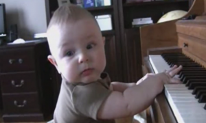 Baby is having a blast on the piano, but when he moves his head—that's when you hear it