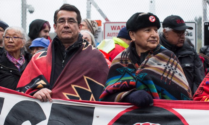 Union of B.C. Indian Chiefs vice president Chief Bob Chamberlin (L) and president Grand Chief Stewart Phillip join protesters opposed to the Kinder Morgan Trans Mountain pipeline expansion in Burnaby, B.C., on April 7, 2018. First Nations in favour of the project are fed up with not being heard. (The Canadian Press/Darryl Dyck)