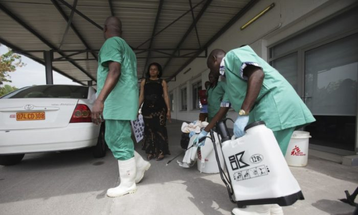 A health worker sprays a colleague with disinfectant during a training session for Congolese health workers to deal with Ebola virus in Kinshasa October 21, 2014. (Reuters/Media Coulibaly)