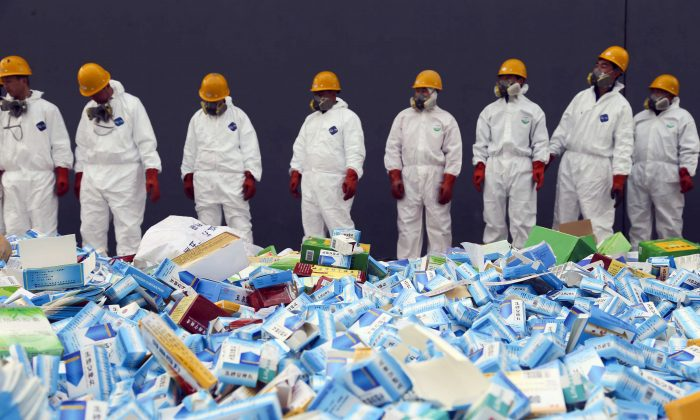 Chinese workers preparing to destroy fake medicines seized in Beijing, on March 14, 2013. Chinese companies are increasingly dominating the manufacturing of the global pharmaceutical market, a development that raises national security concerns in the United States and elsewhere. (STR/AFP/Getty Images)