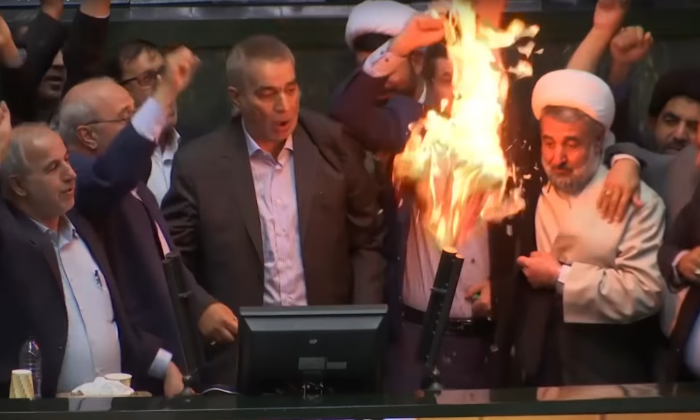 "Iranian lawmakers burn paper American flags while chanting ""Death to America"" on May 8, 2018. (Screenshot)"