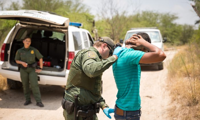A Border Patrol Agent pats down a man who illegally crossed the Rio Grande from Mexico into the United States in Hidalgo County, Texas, on May 26, 2017. (Benjamin Chasteen/The Epoch Times)