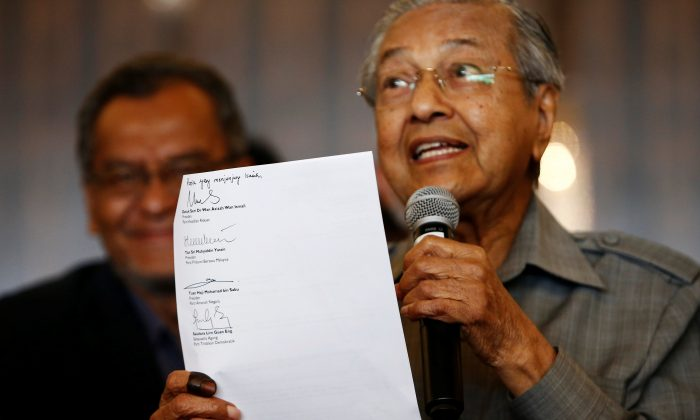 Mahathir Mohamad holds up a document with the signatures of alliance party leaders naming him as the prime minister during a news conference following the general election in Petaling Jaya, Malaysia, May 10, 2018.  (Reuters/Lai Seng Sin)