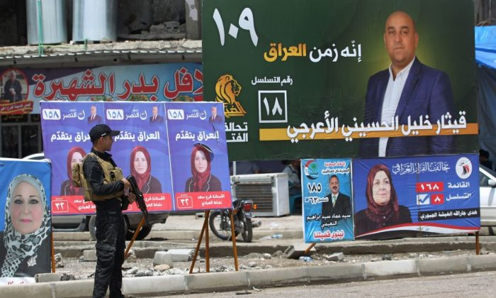 An Iraqi policeman guards a checkpoint by electoral posters in the old town of Mosul on May 11, 2018,       (Ahamd Al-Rubaye/AFP/Getty Images)