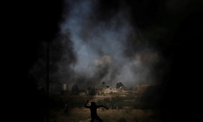 A Palestinian demonstrator uses a sling to hurl stones at Israeli troops during a protest ahead of the 70th anniversary of Nakba, near the Jewish settlement of Beit El, near Ramallah, in the occupied West Bank May 11, 2018. (Reuters/Mohamad Torokman)