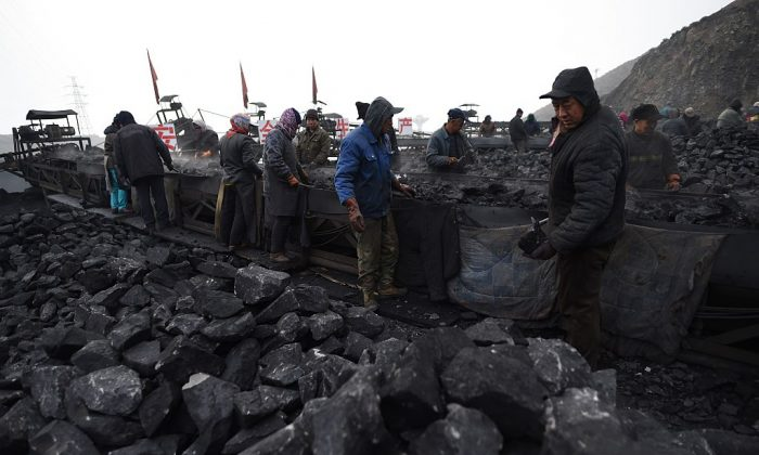 Workers sort coal on a conveyor belt near a coal mine in Datong, in China's northern Shanxi Province on Nov. 20, 2015. (Greg Baker/AFP/Getty Images)