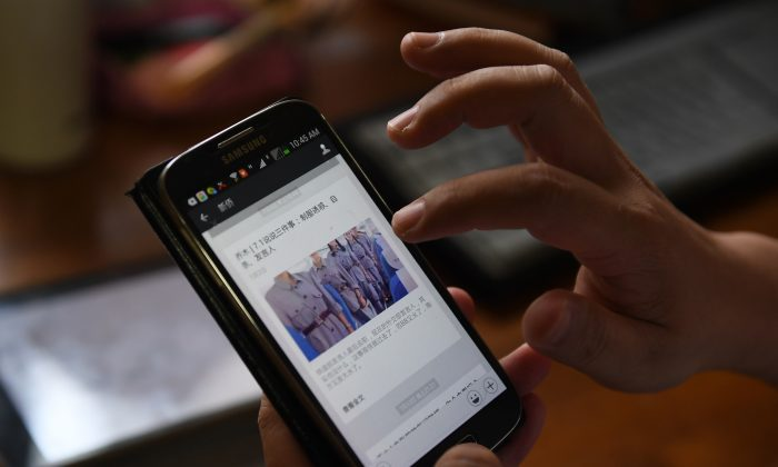 A mobile phone displaying an online post by outspoken professor Qiao Mu, at his home in Beijing, China on July 21, 2017. A new organization made up of Chinese internet companies will assist the Chinese regime in carrying out censorship policies. (Greg Baker/AFP/Getty Images)