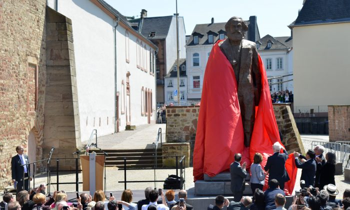 Visitors look on as a statue of German communist thinker Karl Marx is unveiled on May 5, 2018 in his native city of Trier, in southwestern Germany. (HARALD TITTEL/AFP/Getty Images)