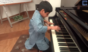 Little boy bowing in front of piano, as soon as he lifts his head—I was not ready for this
