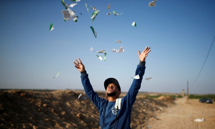 A Palestinian man throws leaflets dropped by the Israeli military during a protest against the U.S. embassy move to Jerusalem and ahead of the 70th anniversary of Nakba, at the Israel-Gaza border, east of Gaza City May 14, 2018. (Reuters/Mohammed Salem)