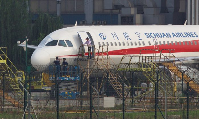 Workers inspect a Sichuan Airlines aircraft that made an emergency landing after a windshield on the cockpit broke off, at an airport in Chengdu, Sichuan province, China May 14, 2018. (Reuters/Stringer)