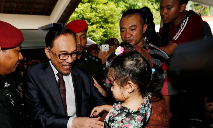 Malaysian politician Anwar Ibrahim greets a child as he arrives at his home after he was granted a full pardon by Malaysia's King Sultan Muhammad V, in Kuala Lumpur, Malaysia May 16, 2018. (Reuters/Lai Seng Sin)