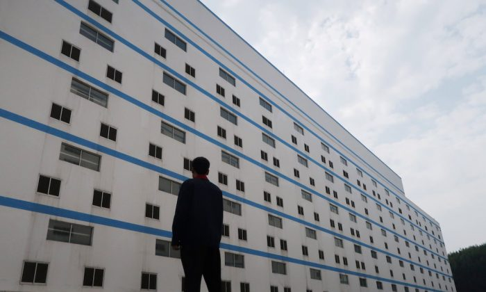A worker poses outside a seven-storey pig building of Guangxi Yangxiang's farm at Yaji Mountain Forest Park in Guangxi province, China, March 21, 2018.( REUTERS/Thomas Suen)