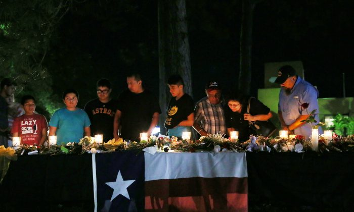 Attendees light candles to pay their respects to the victims of a shooting at Santa Fe High School that left several dead and injured in Santa Fe, Texas, U.S., May 18, 2018.  (Reuters/Pu Ying Huang)