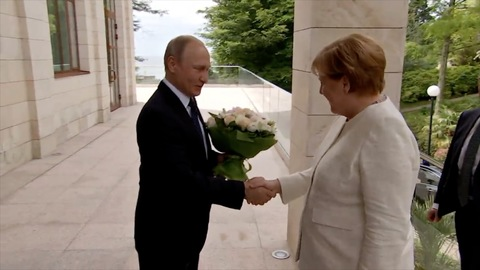 Putin Greets Merkel With White Rose Bouquet in Sochi