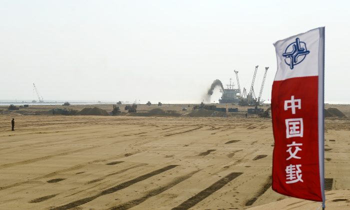 "Pumps dredging sand at the site of a Chinese-funded $1.4 billion reclamation project next to the Colombo main sea port on January 2, 2018. China has several infrastructure projects planned as part of its ""One Belt, One Road"" initiative for spreading its geopolitical influence. (Lakruwan Wanniarachchi/AFP/Getty Images)"