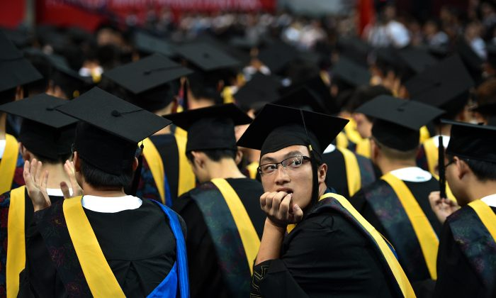 Students at the Huazhong University of Science and Technology graduation ceremony in a sports stadium in Wuhan City, in China's central Hubei Province, on June 20, 2017. (STR/AFP/Getty Images)