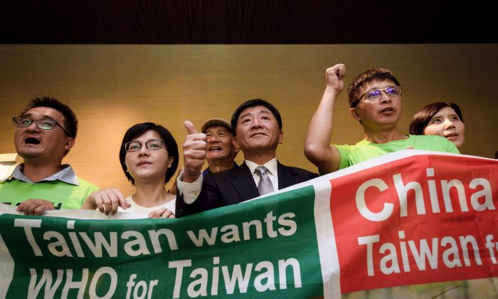 Taiwan's health Minister Chen Shih-chung (C) gives a thumb up as he poses with demonstrators after a press conference on the sideline of the World Health Organization annual Assembly on May 21, 2018 in Geneva. (Fabrice COFFRINI / AFP)