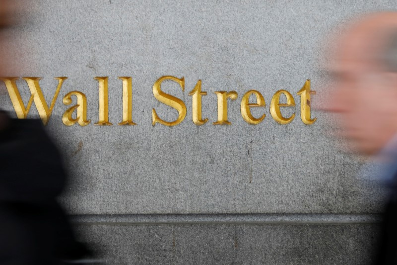 People walk by a Wall Street sign close to the New York Stock Exchange in New York
