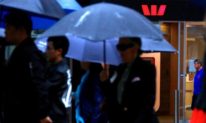 Pedestrians hold umbrellas as they walk past a branch of the Westpac Banking Corp in central Sydney, Australia, March 30, 2017. (Reuters/David Gray/File Photo)