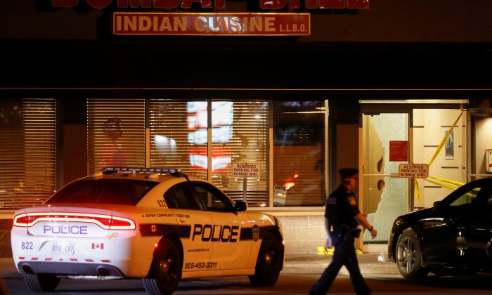 A police officer walks in front of Bombay Bhel restaurant, where two unidentified men set off a bomb late Thursday night, wounding more than a dozen people, in Mississauga, Ontario, Canada May 25, 2018. (Reuters/Mark Blinch)
