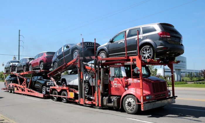A car hauler transports Chrysler vehicles from the FCA Jefferson North Assembly Plant in Detroit, Michigan on May 25, 2018.  (REUTERS/Rebecca Cook)