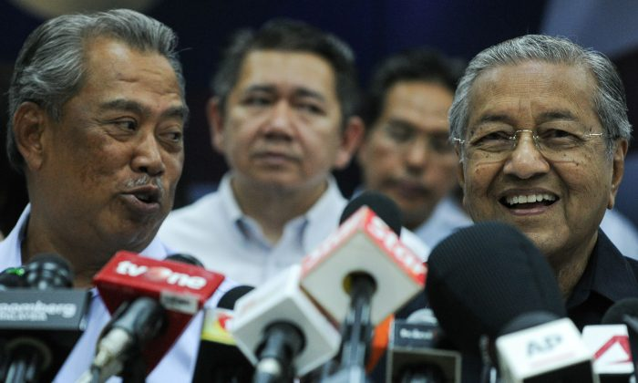 Mahathir Mohamad (R) and former Malaysian deputy prime minister Muhyiddin Yassin (L) talk to each other before a press conference with members of the opposition party in Kuala Lumpur on March 4, 2016. (MOHD RASFAN/AFP/Getty Images)