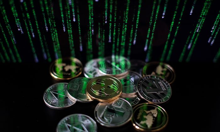 A photo illustration of ripple, litecoin, and ether digital tokens is seen April 25, 2018, in London. Despite their perceived potential, blockchain technologies face immense roadblocks to widespread adoption. (Jack Taylor/Getty Images)
