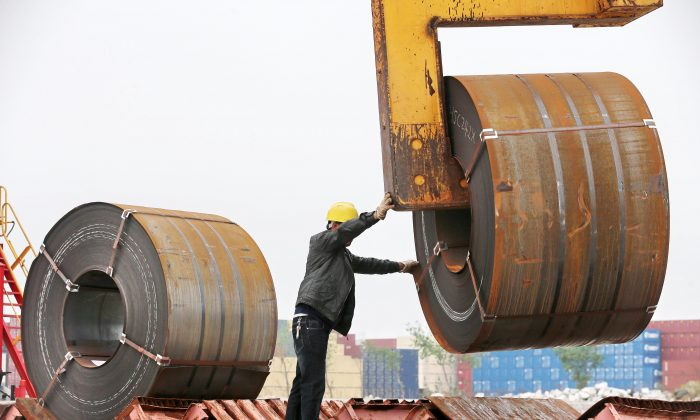 A worker uses a crane to lift a roll of steel at a shipyard in Nantong City, in China's eastern Jiangsu Province, on May 19, 2018. (AFP/Getty Images)