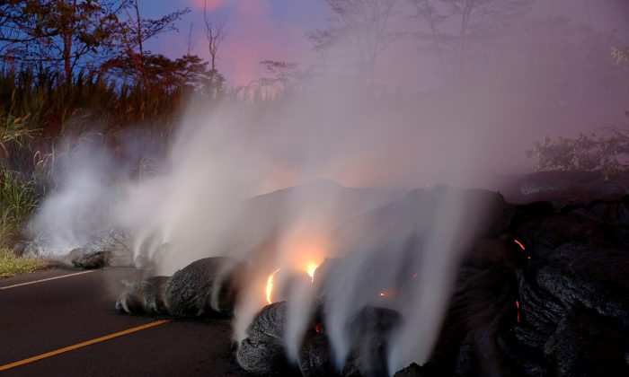 Volcanic gases rise from the Kilauea lava flow that crossed Pohoiki Road near Highway 132, near Pahoa, Hawaii, May 28, 2018. (Reuters/Marco Garcia)