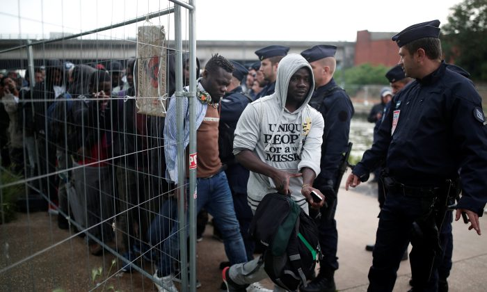 Migrants prepare to leave as French police evacuate hundreds of migrants living in makeshift camps in Paris, France, May 30, 2018.  (Reuters/Benoit Tessier)