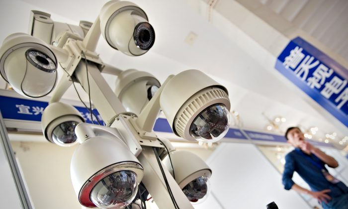 A man stands by a display of surveillance cameras at an international exhibition on public security in Shanghai on April 27, 2011.  (Philippe Lopez/AFP/Getty Images)