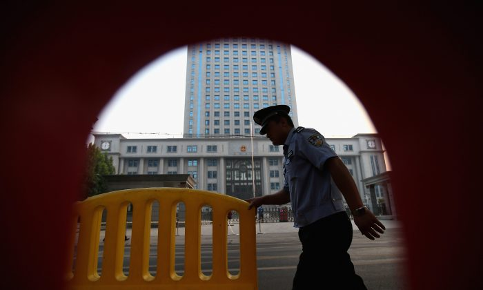 A policeman passing a court in Jinan City, China on August 22, 2013. (Feng Li/Getty Images)