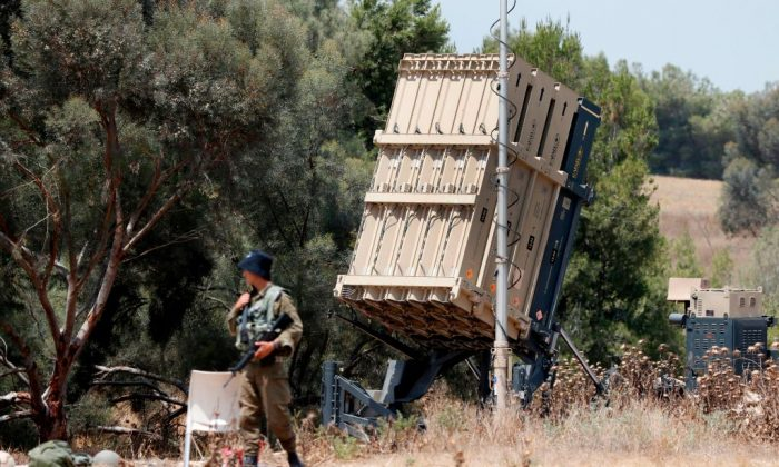 Israeli soldiers stand guard next to an Israeli Iron Dome defence system, designed to intercept and destroy incoming short-range rockets and artillery shells, deployed along the border with the Gaza strip on May 29, 2018. (JACK GUEZ/AFP/Getty Images)
