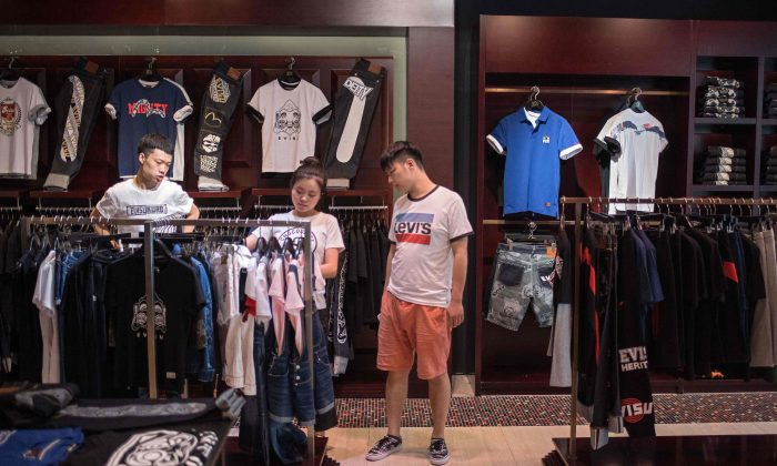 People shop for clothing at a shopping mall in Beijing on May 10, 2018. (Nicolas Asfouri/AFP/Getty Images)