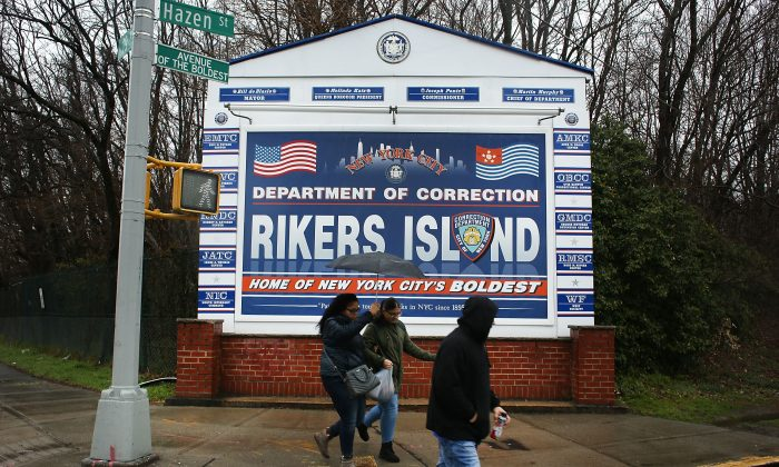 People walk by a sign at the entrance to Rikers Island in New York City on March 31, 2017. (Spencer Platt/Getty Images)