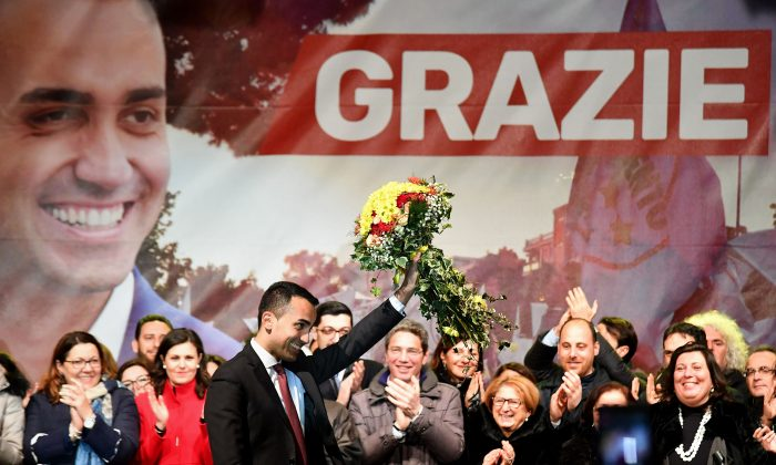 Italy's populist Five Star Movement (M5S) party leader Luigi Di Maio (C) waves flowers as he celebrates with supporters in his home town of Pomigliano on March 6, 2018, after Italy's general elections. (ALBERTO PIZZOLI/AFP/Getty Images)