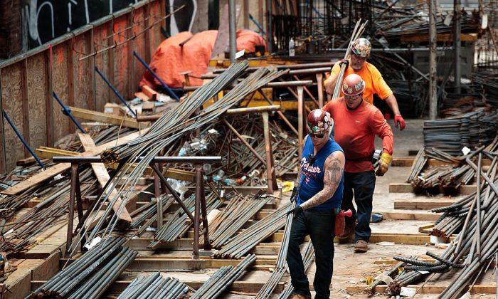 Construction laborers work on the site of a new residential building in the Hudson Yards development in New York City on Aug. 16, 2016. With the tightening labor market, there are not enough Americans available to take infrastructure jobs, say industry experts. (Drew Angerer/Getty Images)