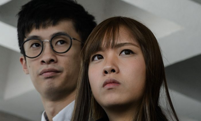 Former Hong Kong lawmakers Baggio Leung (L) and Yau Wai-ching speak to the press outside the High Court in Hong Kong on November 30, 2016. They were recently sentenced to a four-week jail term. (Anthony Wallace/AFP/Getty Images)