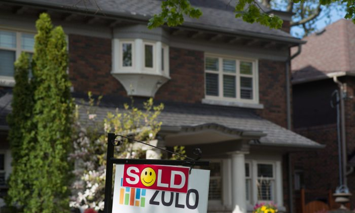 A sold sign is shown in front of a west-end Toronto home in this file photo. The housing bubbles in Vancouver and Toronto appear to be gradually deflating, but affordability is still extremely poor. (The Canadian Press/Graeme Roy)