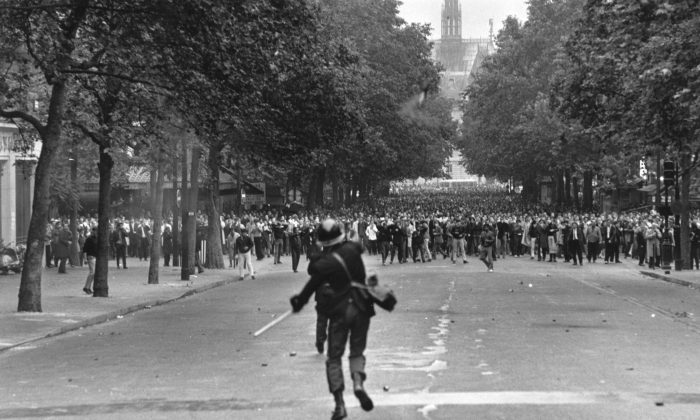 A policeman throws a tear gas canister to disperse crowds during student riots in Paris in the summer of 1968. The student protesters thought they would liberating people from consumer society, but ended up building a culture addicted to consumption  (Reg Lancaster/Getty Images)