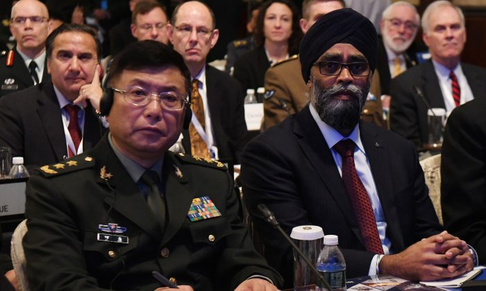 Lt. Gen. He Lei (L), vice president of the People's Liberation Army's Academy of Military Science, and Hajit Sajjan (R), Canadian National Defense Minister, attend the first plenary session of the 17th Asian Security Summit of the IISS ShangriLa Dialogue in Singapore on June 2, 2018. (Roslan Rahman/AFP/Getty Images)
