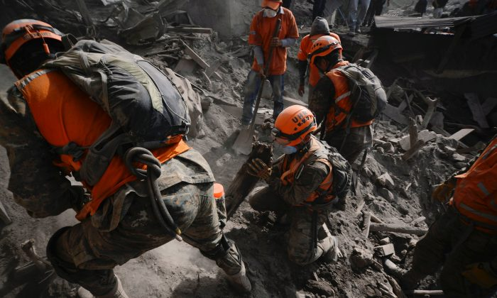 Soldiers search for remains at an area affected by the eruption of the Fuego volcano at El Rodeo in Escuintla, Guatemala June 6, 2018. (Reuters/Fabricio Alonzo)