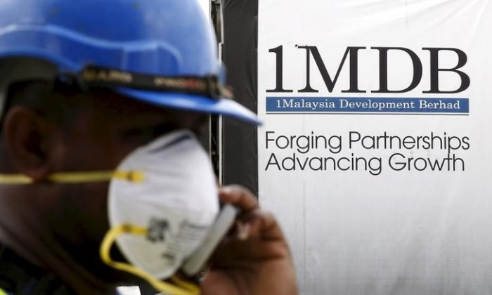 A construction worker talks on the phone in front of a 1Malaysia Development Berhad (1MDB) billboard at the Tun Razak Exchange development in Kuala Lumpur, Malaysia, in this Feb. 3, 2016 file photo. (Reuters/Olivia Harris/Files)