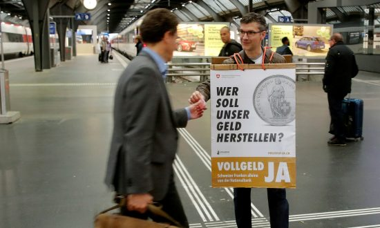 A member of the sovereign money initiative, a referendum campaign that would abolish traditional bank lending and allow only money created by the Swiss National Bank, offers flyers to travelers at the central railway station in Zurich, Switzerland, May 3, 2018. (Reuters/Arnd Wiegmann/File Photo)