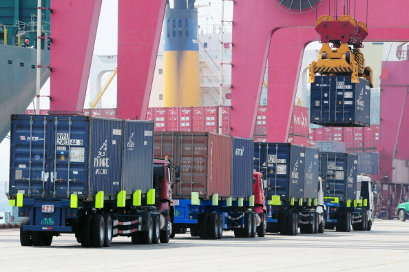 Trucks preparing to load and unload shipping containers in a port in Qingdao, in eastern China's Shandong Province, on April 10, 2013. (STR/AFP/Getty Images)