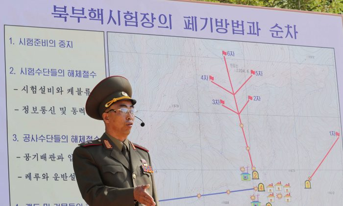 In this handout image provided by the News1-Dong-A Ilbo, a North Korean soldier explains the demolition process of the Punggye-ri nuclear test facility to the media at the Punggye-ri nuclear test site on May 24, 2018 in Punggye-ri, North Korea. (News1-Dong-A Ilbo via Getty Images)
